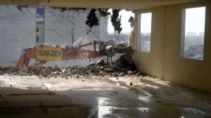 widok na maszynę burzącą z wnętrza budynku