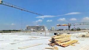 żurawie wieżowe widziane z dachu prowadzonej inwestycji