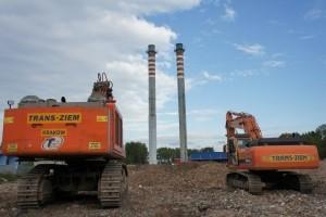 ciężki sprzęt trans-ziem na tle burzonych kominów