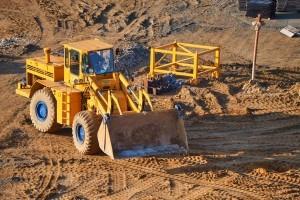 ładowarka ładuje samochody ciężarowe piaskiem
